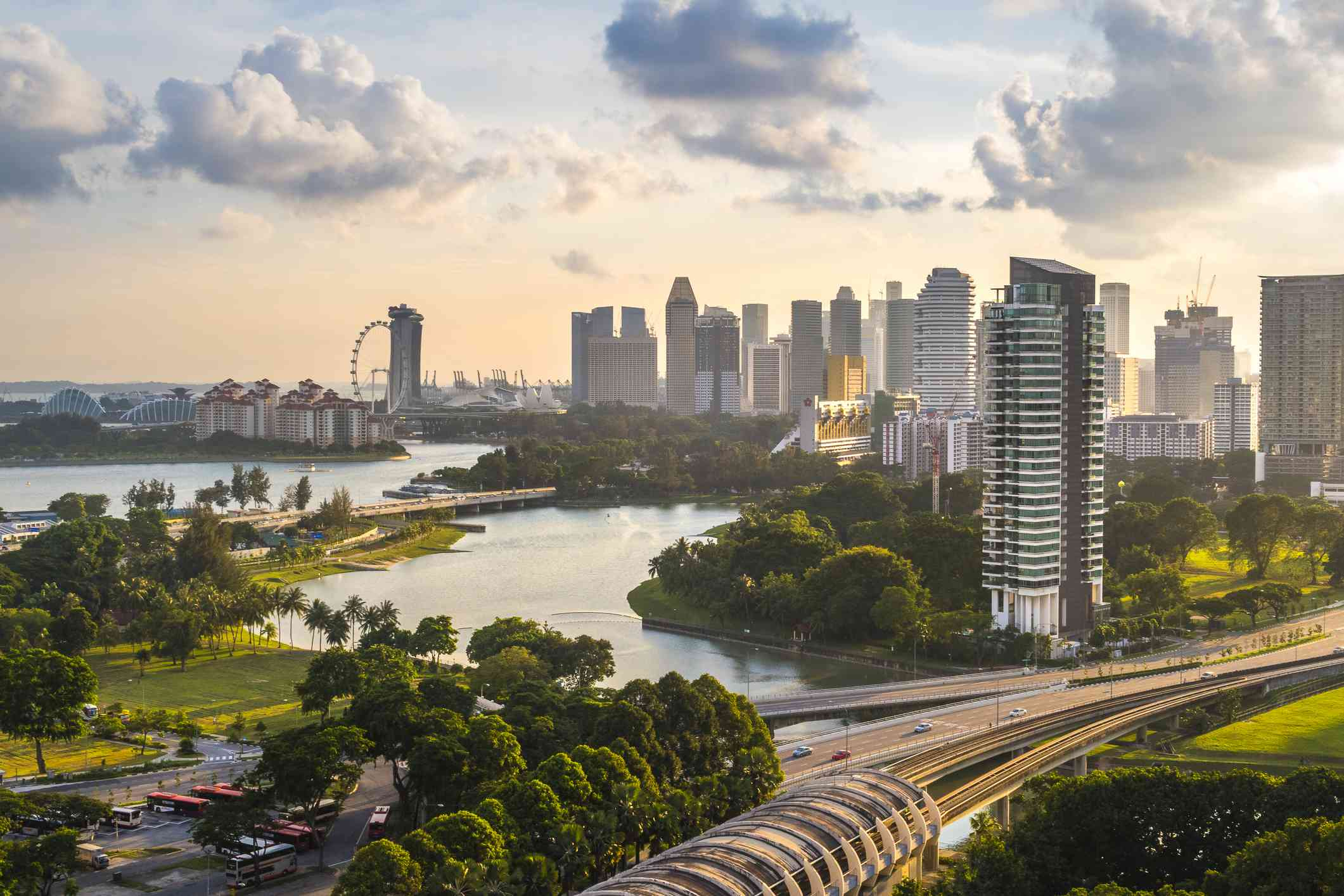 Downtown Singapore high rise buildings next to lush green trees and waterways under a sunny sky with white clouds