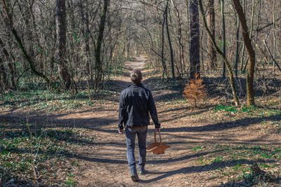 man stands alone in woods at a dirt road crossway with a basket in hand