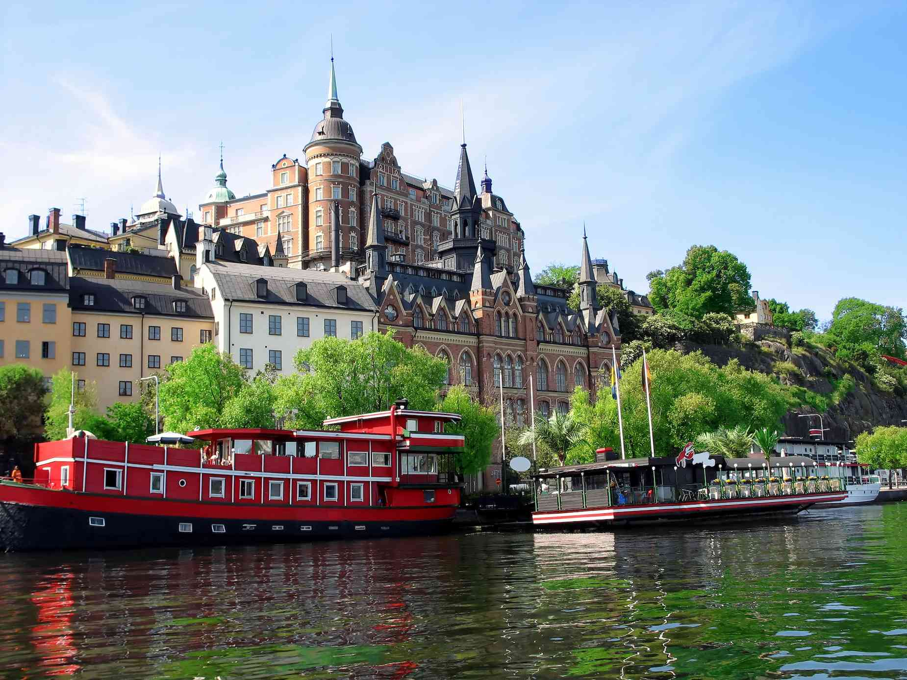 large red boat on waterway in Stockholm, Sweden