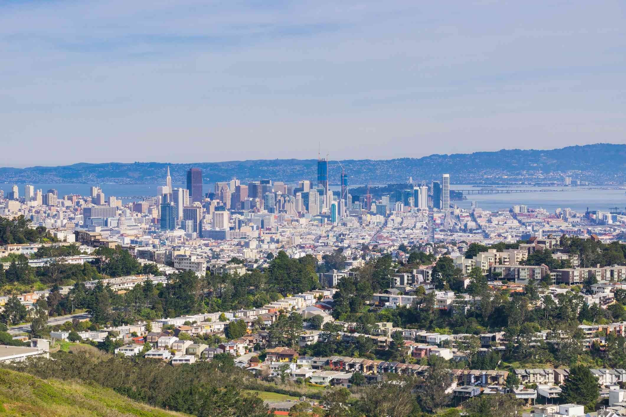 View of the city of San Francisco from Mt Davidson, with blue sky, and smaller mountains in the distance, the tall buildings of the city center and smaller buildings in the foreground located among tall green trees