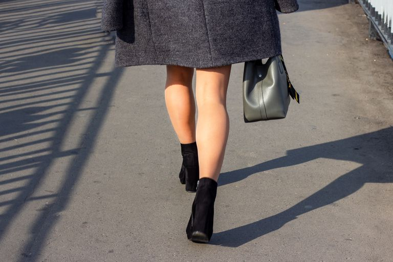 Bare legs walking in the city with a grey coat and heels.