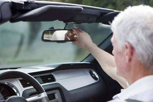 older driver adjusts the rearview mirror