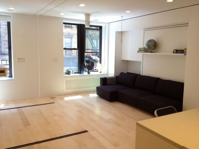 Modern living room design with white walls, black sofa and wood floors