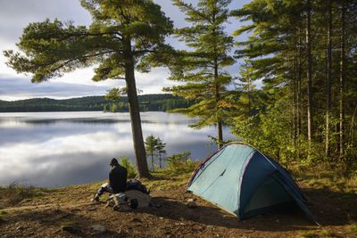 Man sitting on a rock next to a tent with a view of Provoking Lake in Algonquin Provincial Park