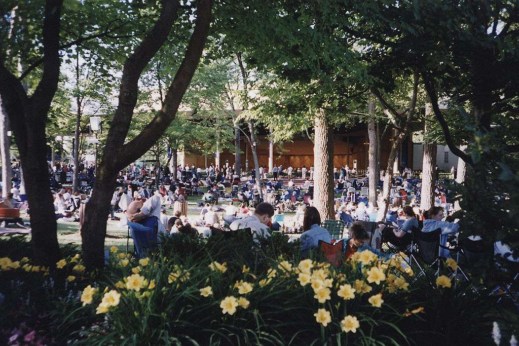 View of Ravinia Pavillion with yellow flowers and shade trees in the foreground between concert-goers and the pavillion