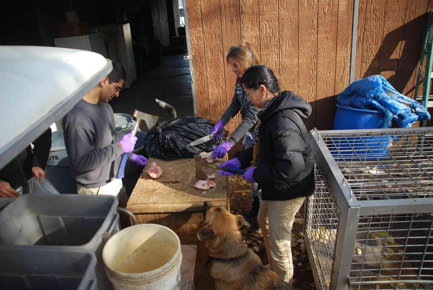 LARC volunteers cut up raw meat