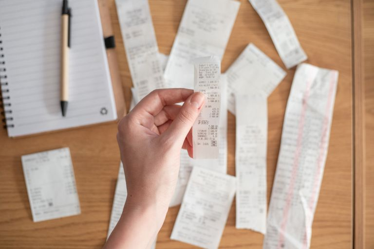 hand holds up paper receipt to camera, with multiple receipts on wooden desk background