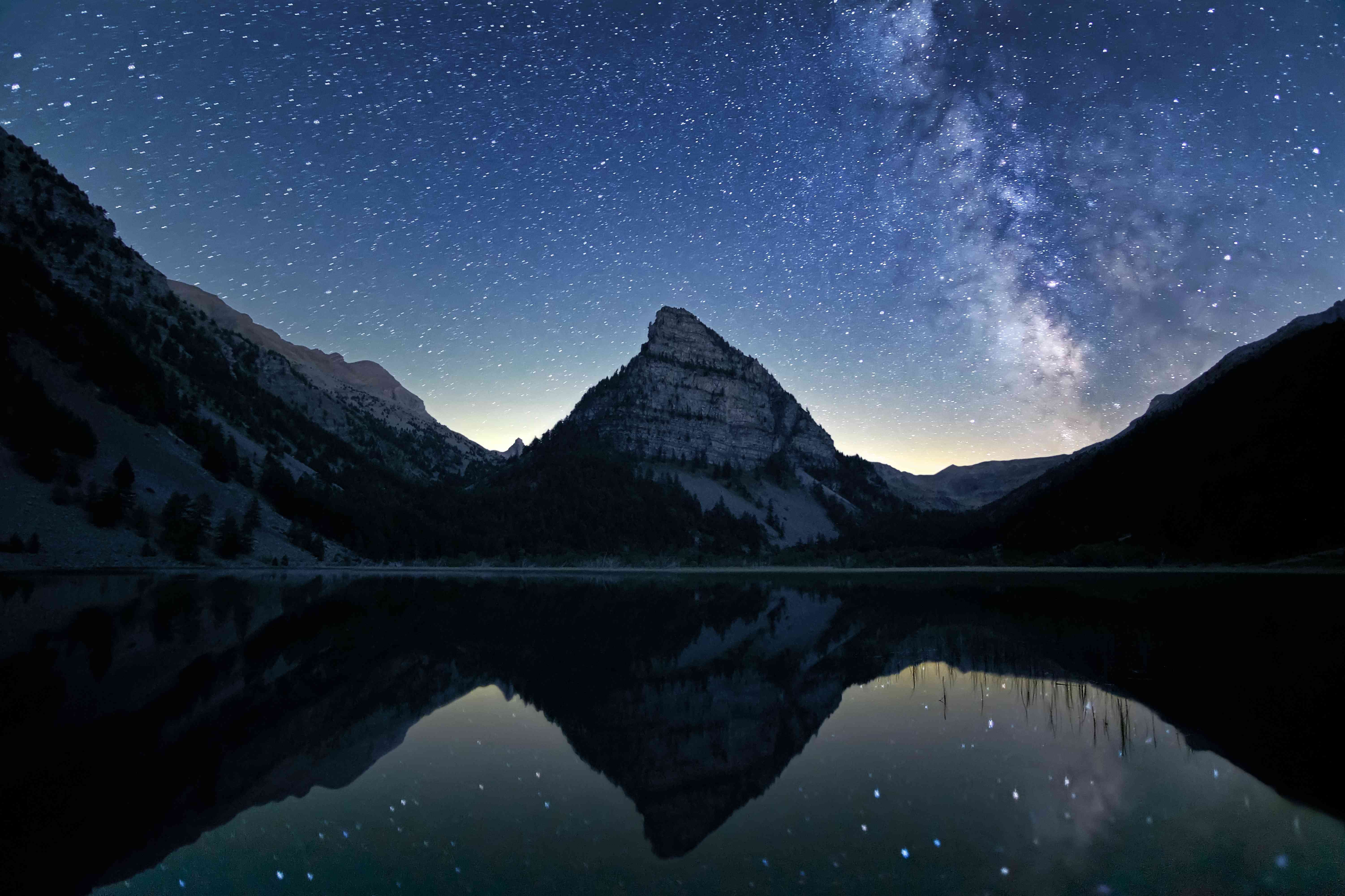 Milky Way and stars above snowy mountain and lake