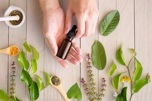 Hands holding dropper bottle over flat lay of botanical ingredients