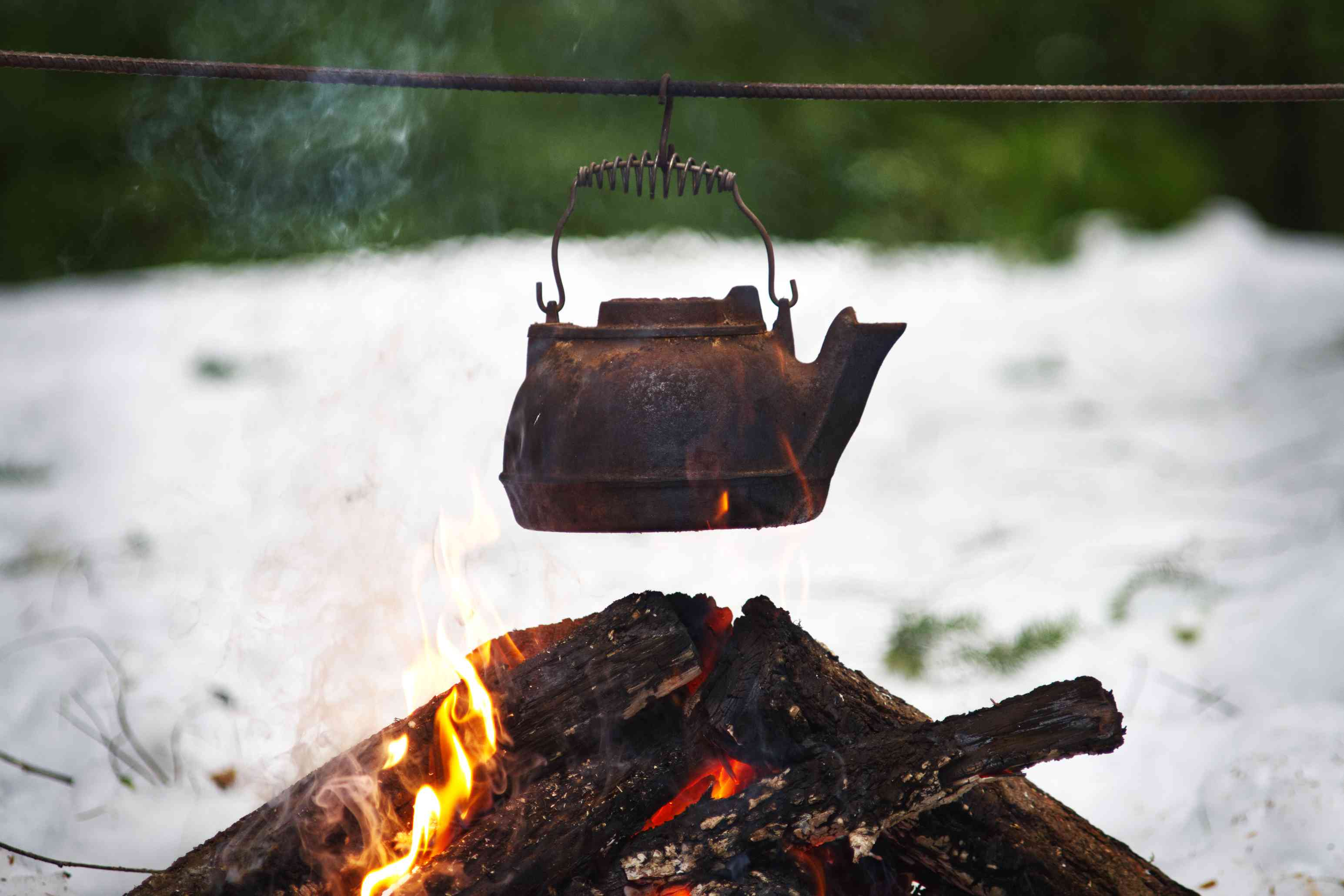 oil iron kettle cooking over campfire in snow