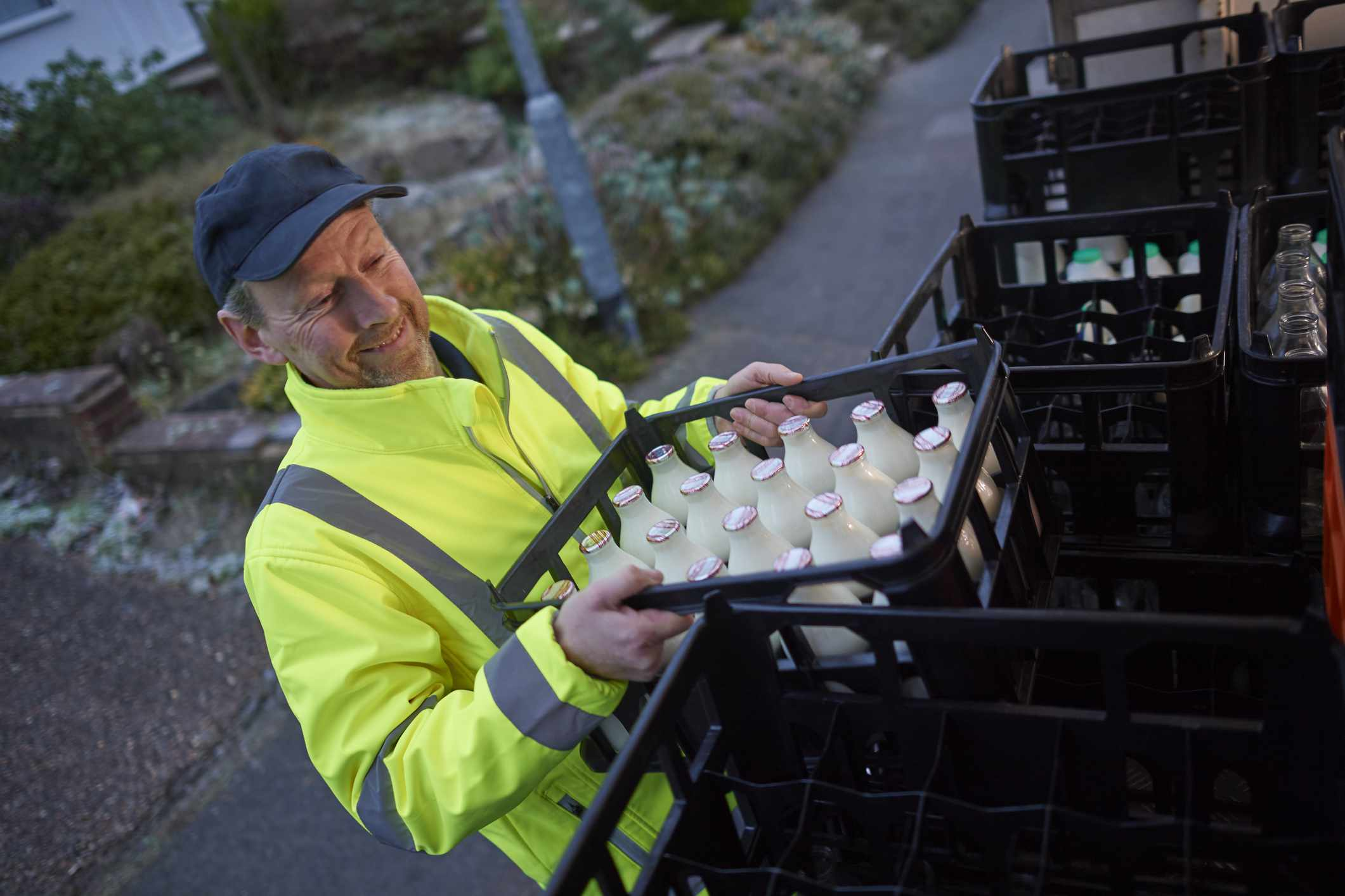 A milkman carries a crate full of bottles of milk of a truck.