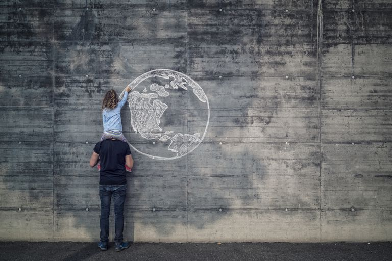 Austria, Salzburg, Father with daughter on his shoulders, the daughter draws with chalk the earth on a concrete wall