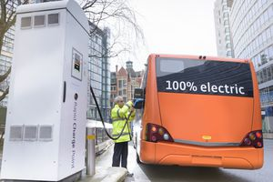 Bus driver charging electric bus at charging station