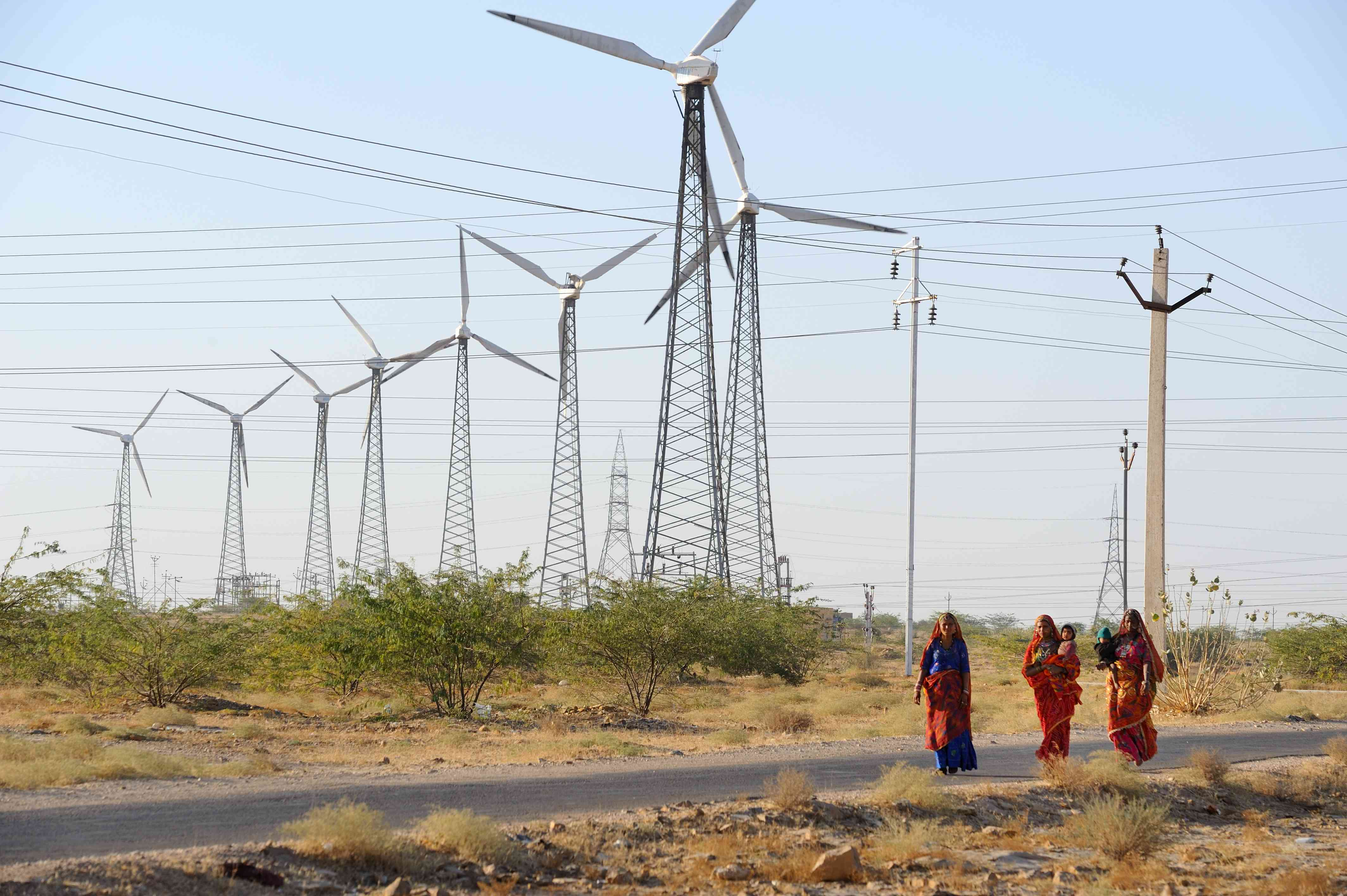 Young women walk in front of windmills in India's Jaisalmer region in Rajasthan.