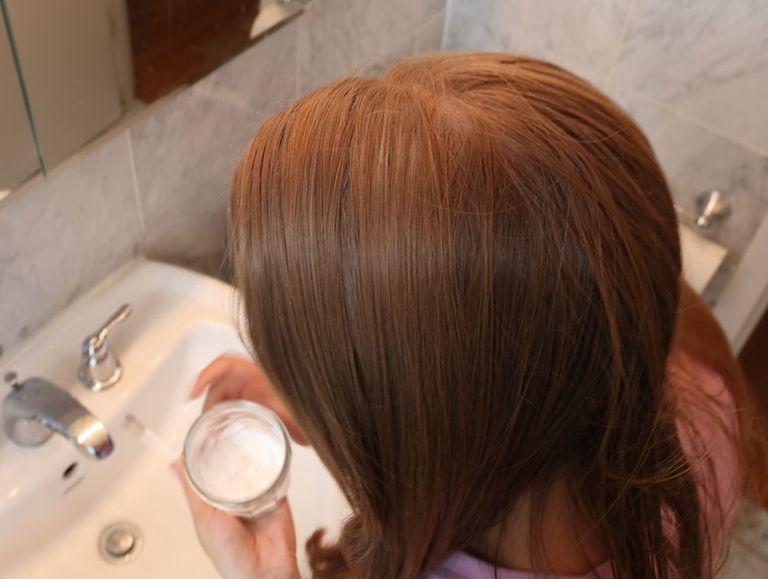 A redhead applies a mixture to her hair.