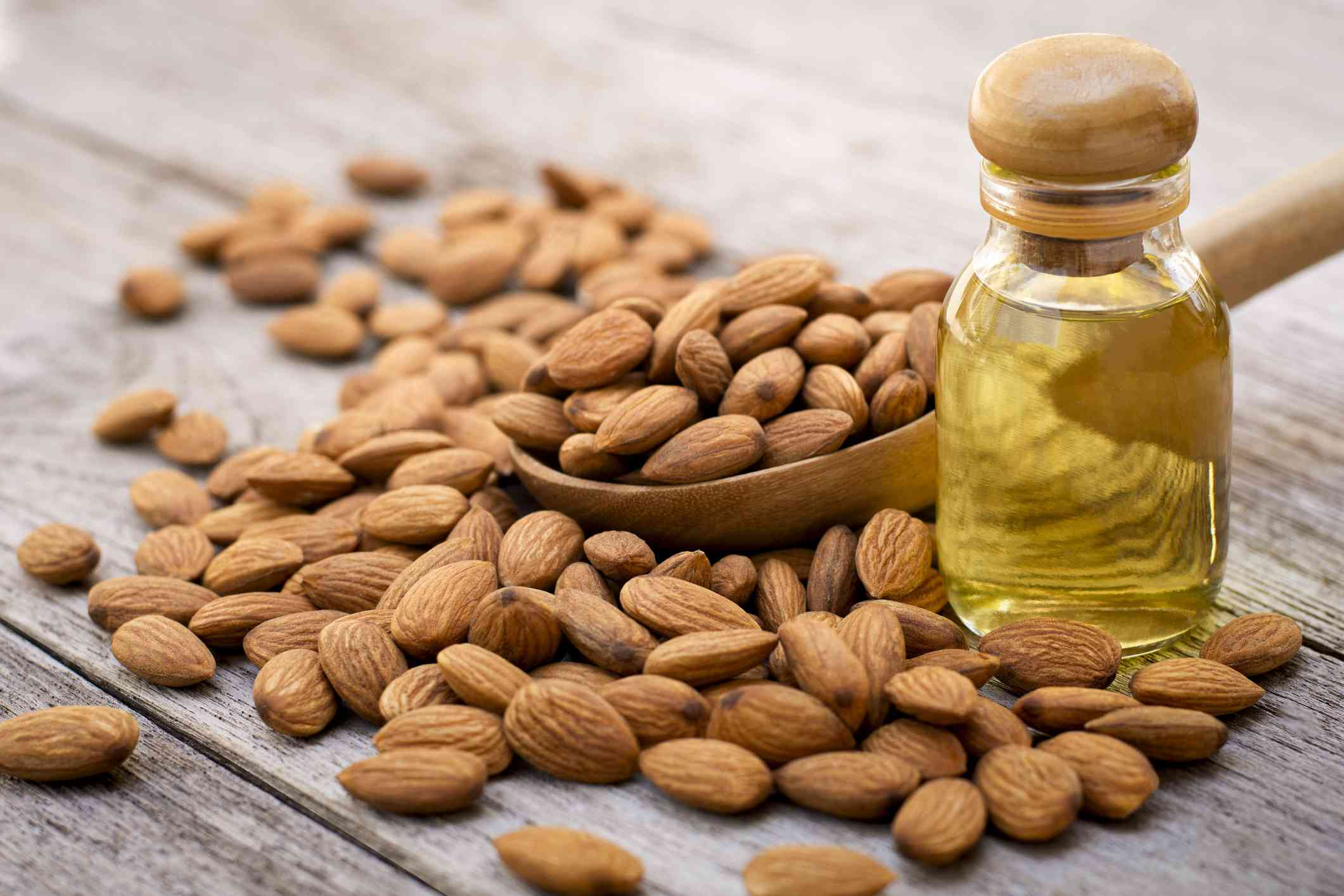 Closeup almond oil in glass bottle and group of almond nuts in wooden spoon isolated on wood table background.