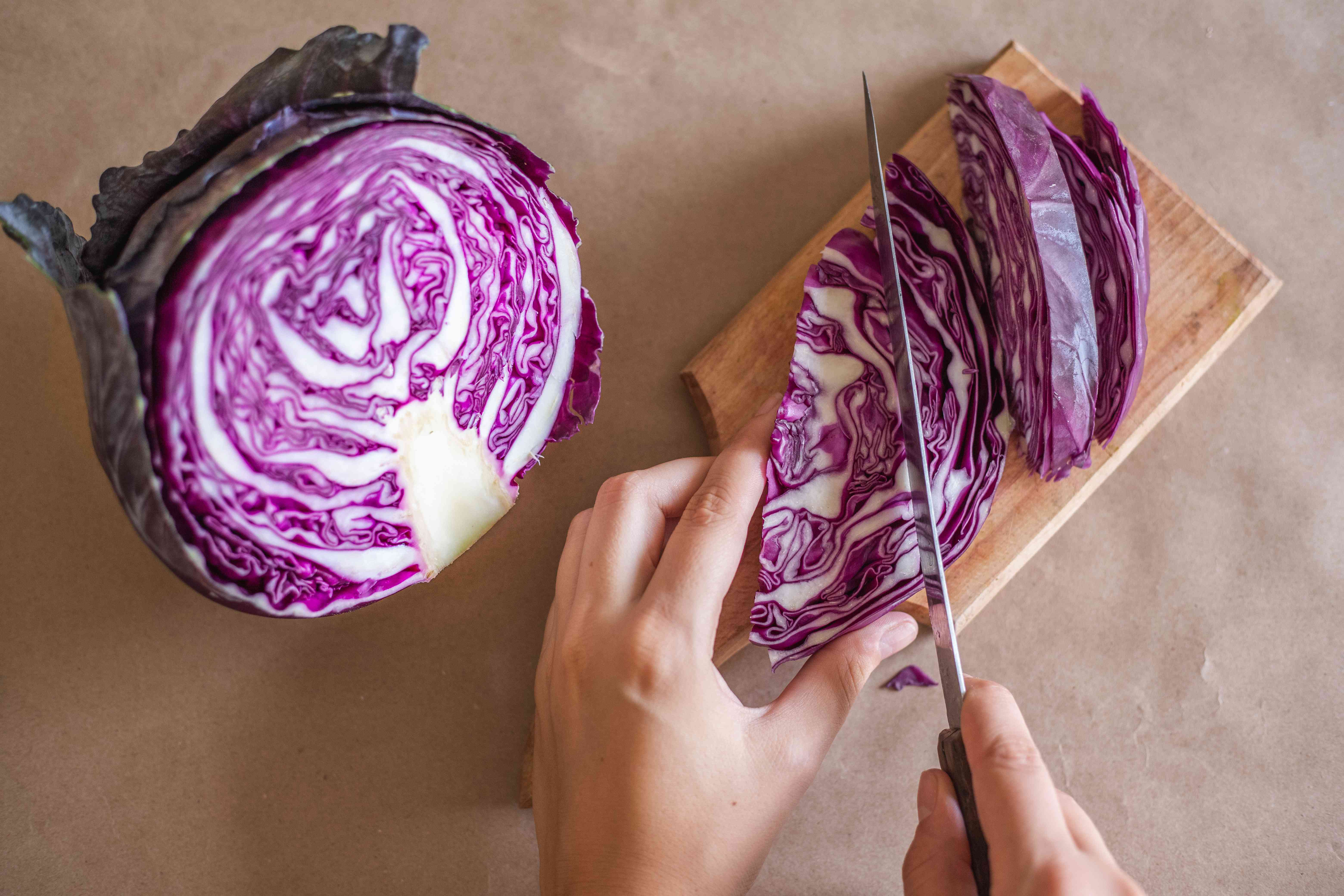 hands chop red cabbage into strips on wooden cutting board