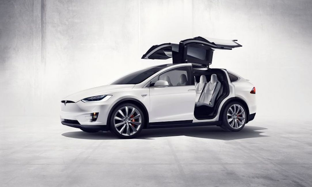White Tesla car with doors and roof open