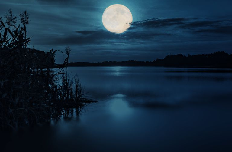 The moon over a lake at night.