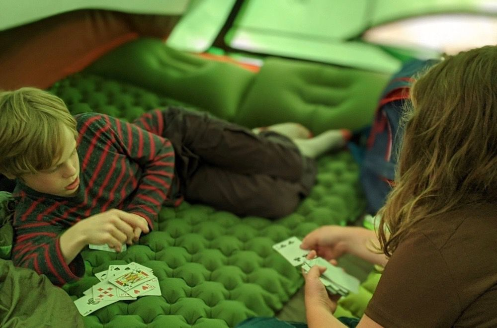kids playing cards in a tent