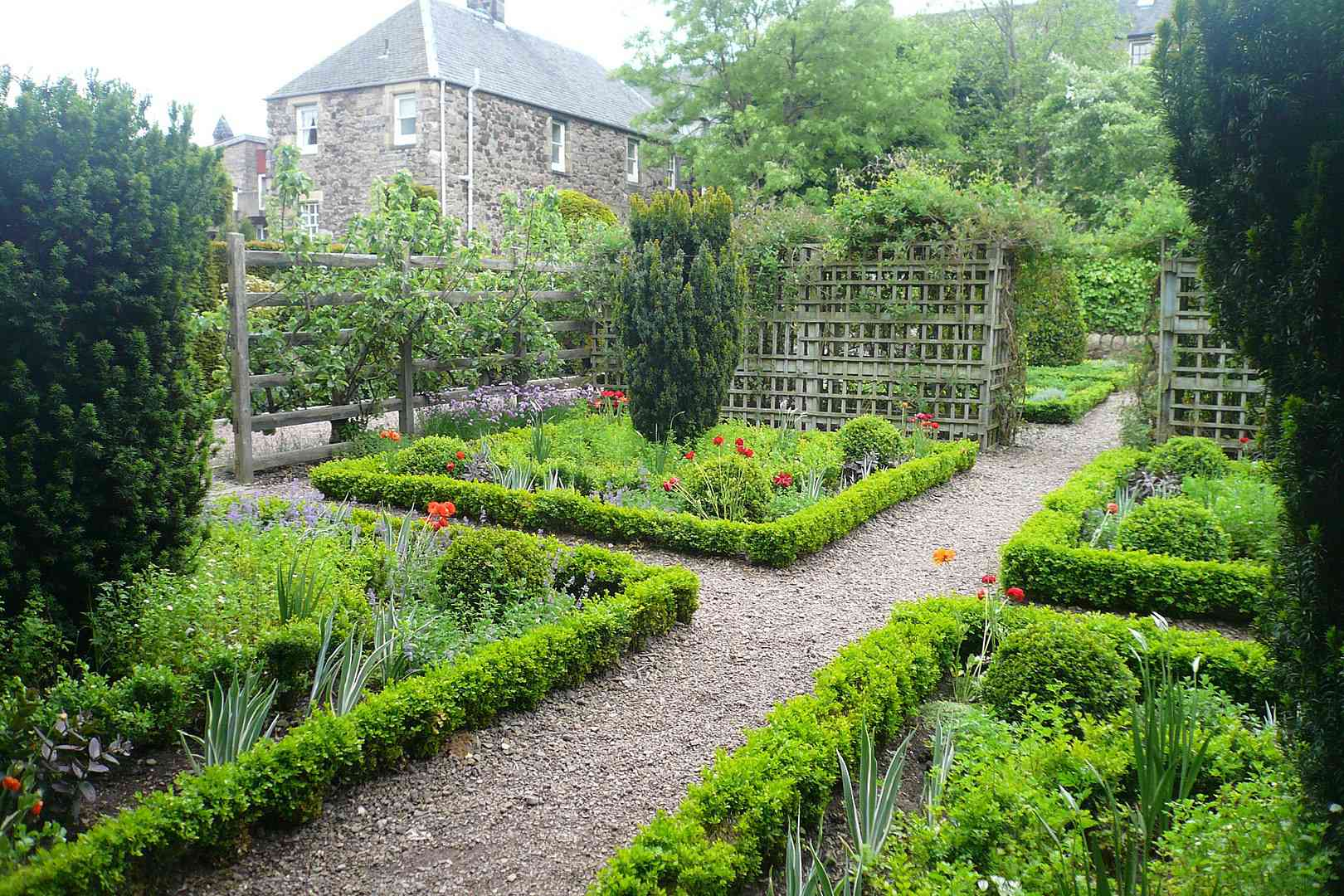 Paths through Dunbar's Close Garden, an orderly garden with small, green ground cover lining plant beds filled with larger green plants and tall shaped bushes with a wood trellis and a small church in the distance