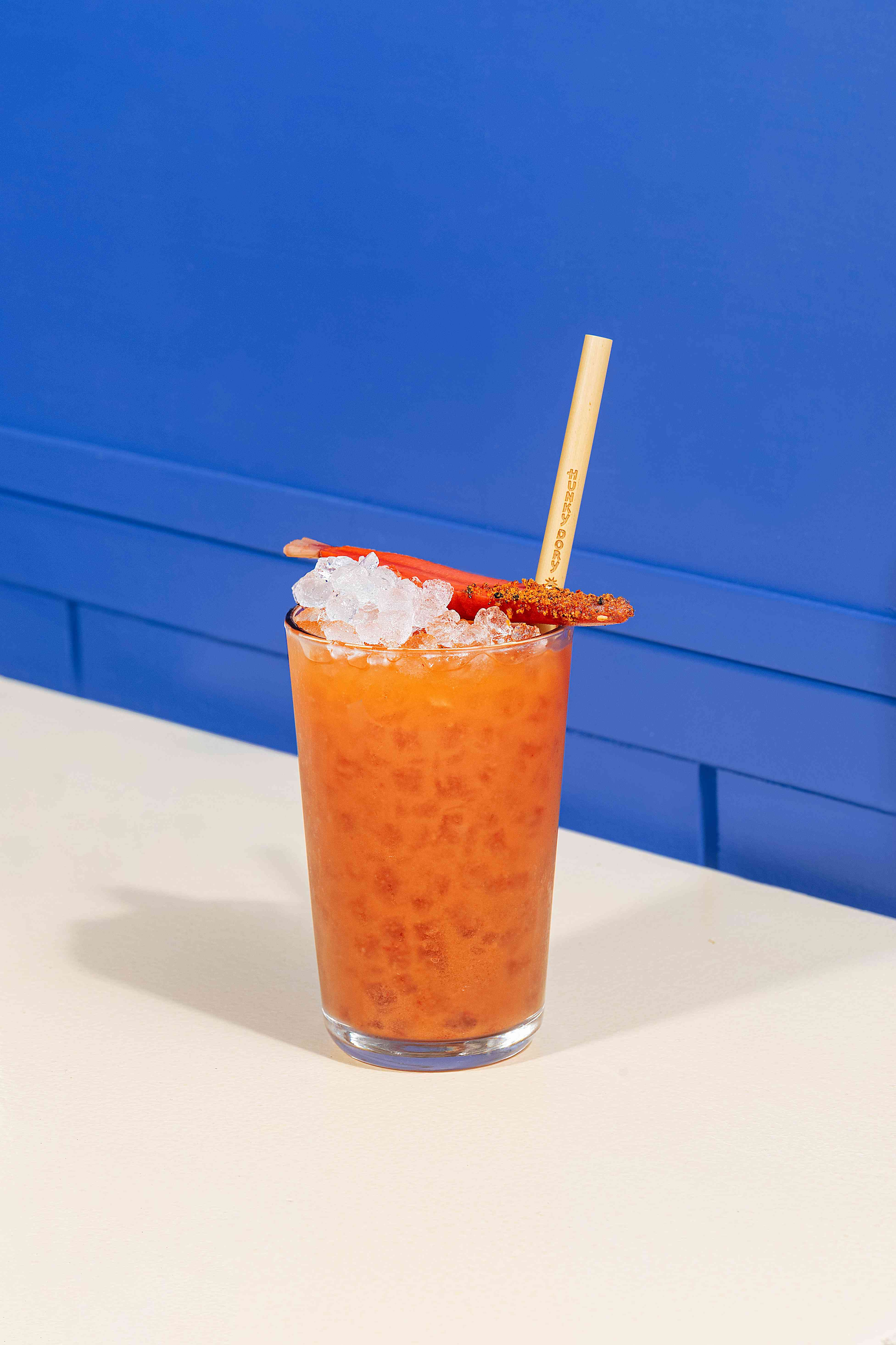 A Bloody Mary cocktail made with carrots and spice on table