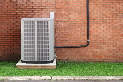 Air conditioning unit outside against a brick wall
