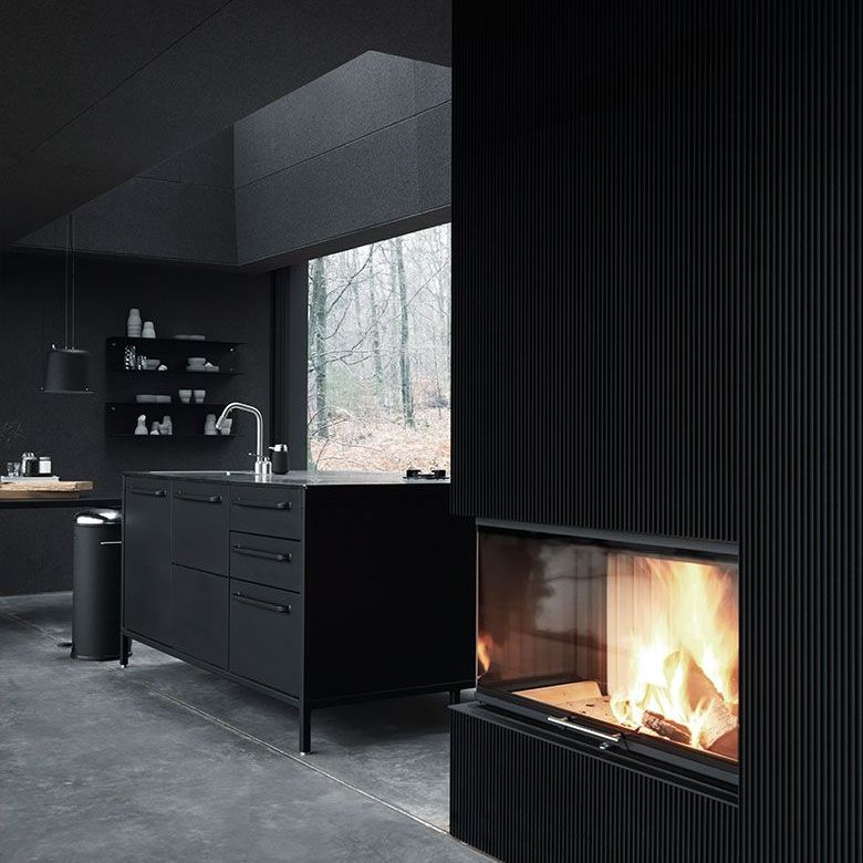 Dark gray kitchen with fireplace in the foreground and island in the back