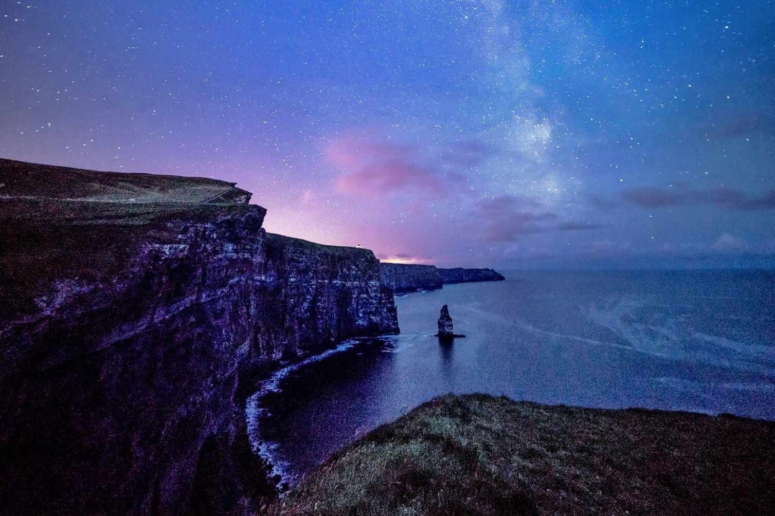 Stars and pink clouds over ocean and rocky cliffs