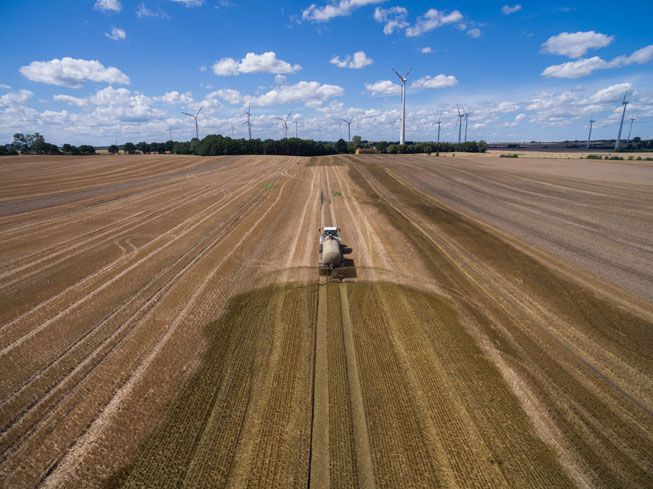 A truck spreads fertilizers on a field in Germany with wind turbines stand on the horizon