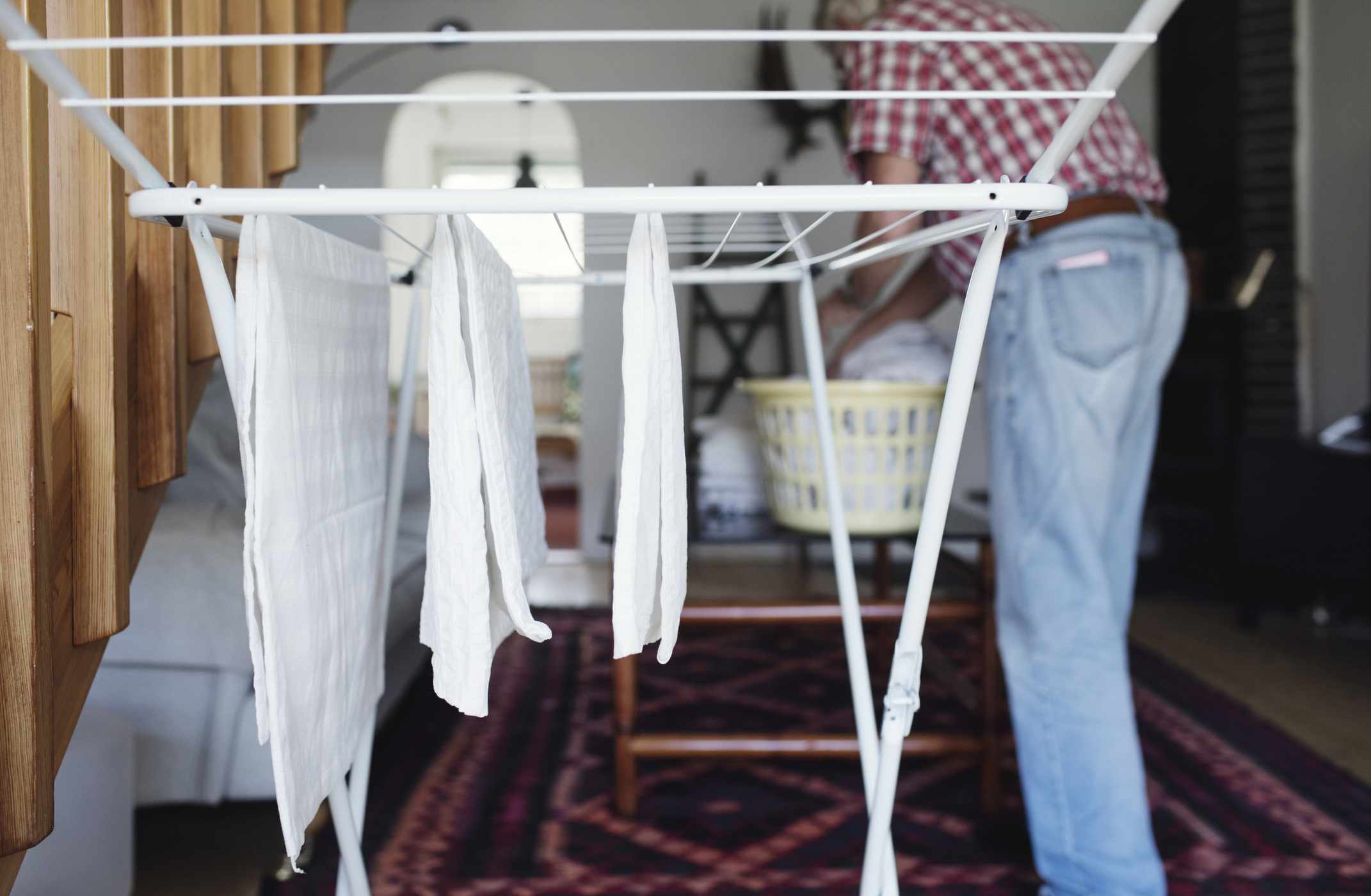 A person hanging white clothes on an indoor clothesline.