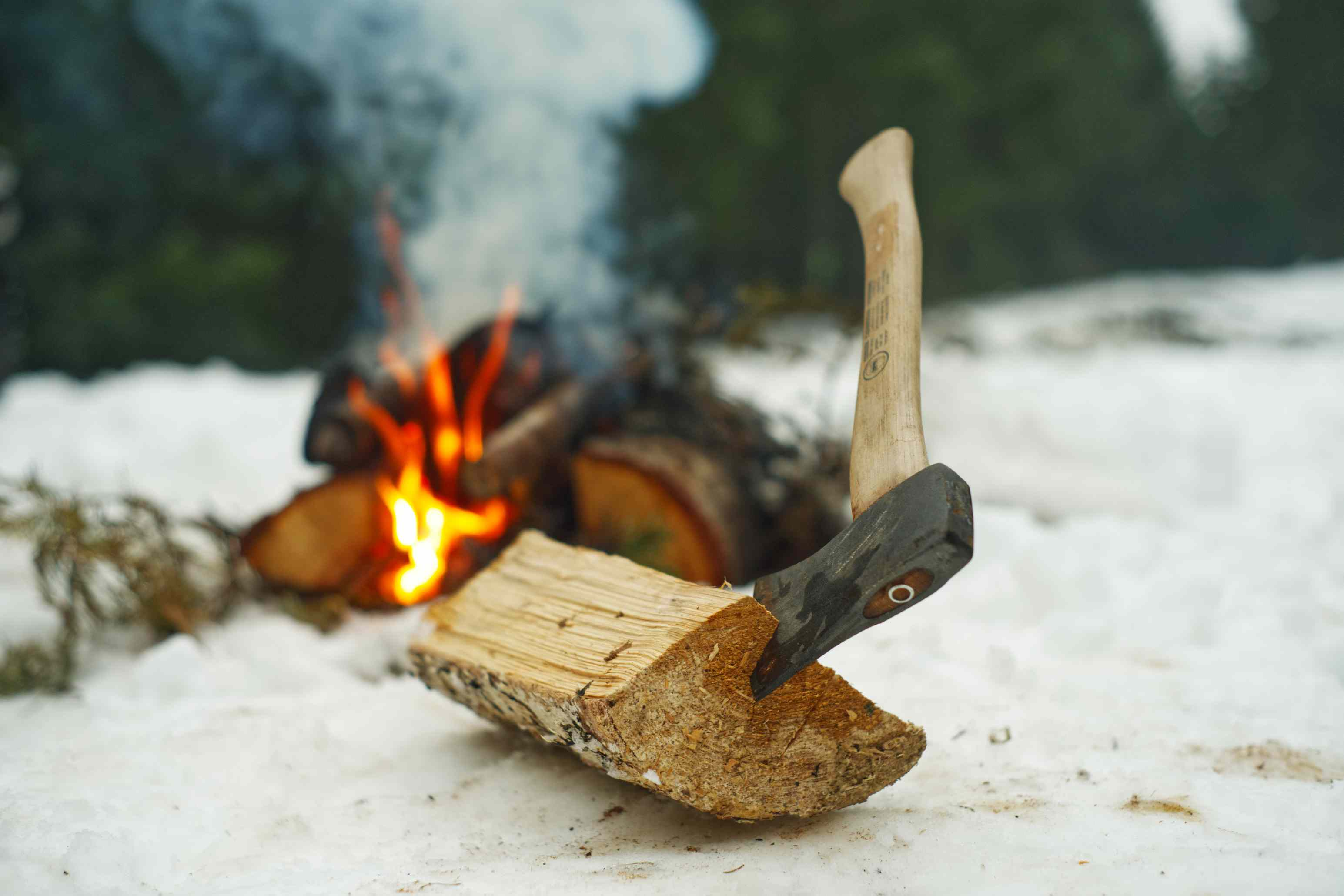 large axe in firewood next to campfire in snow