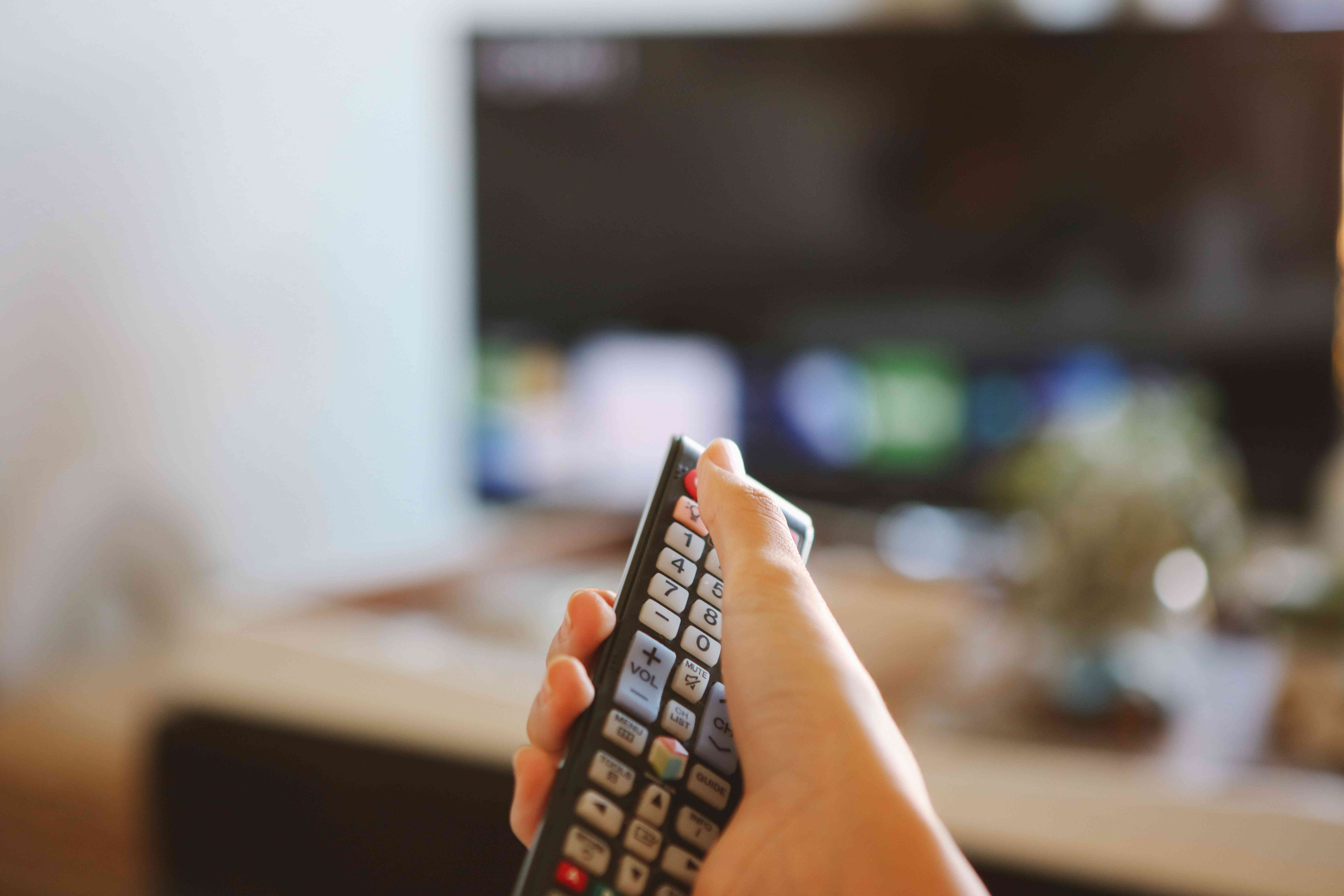 hand holds remote to turn tv off