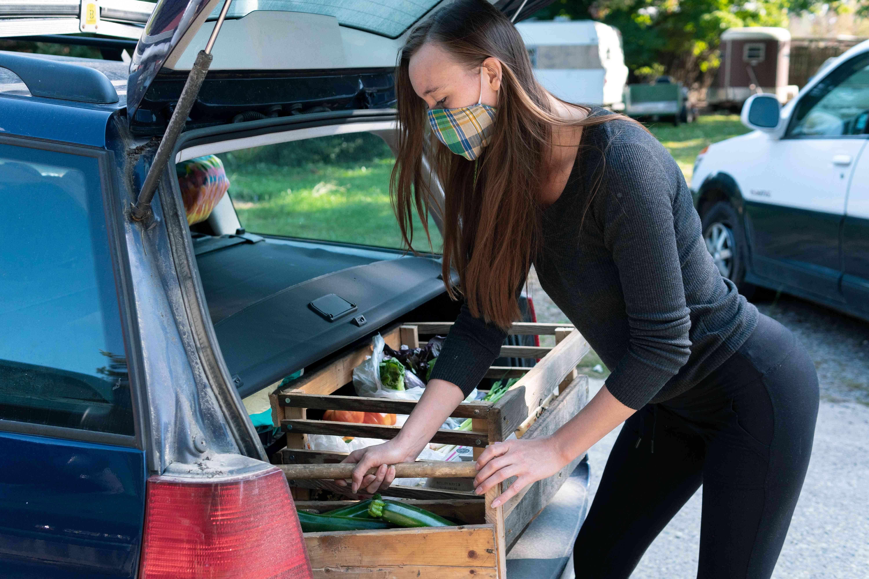 woman unloads farm produce out of car