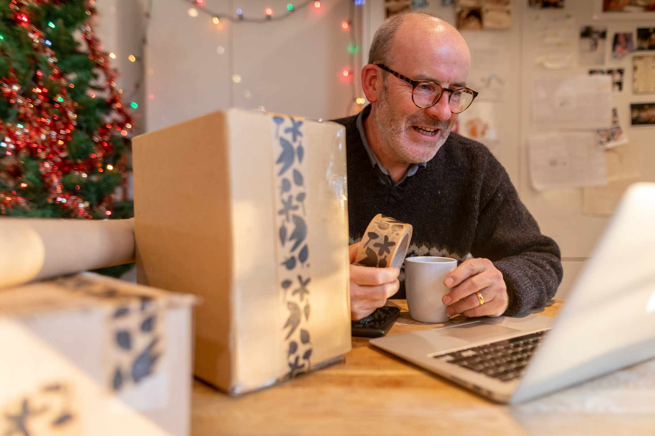Man wrapping parcels and using laptop