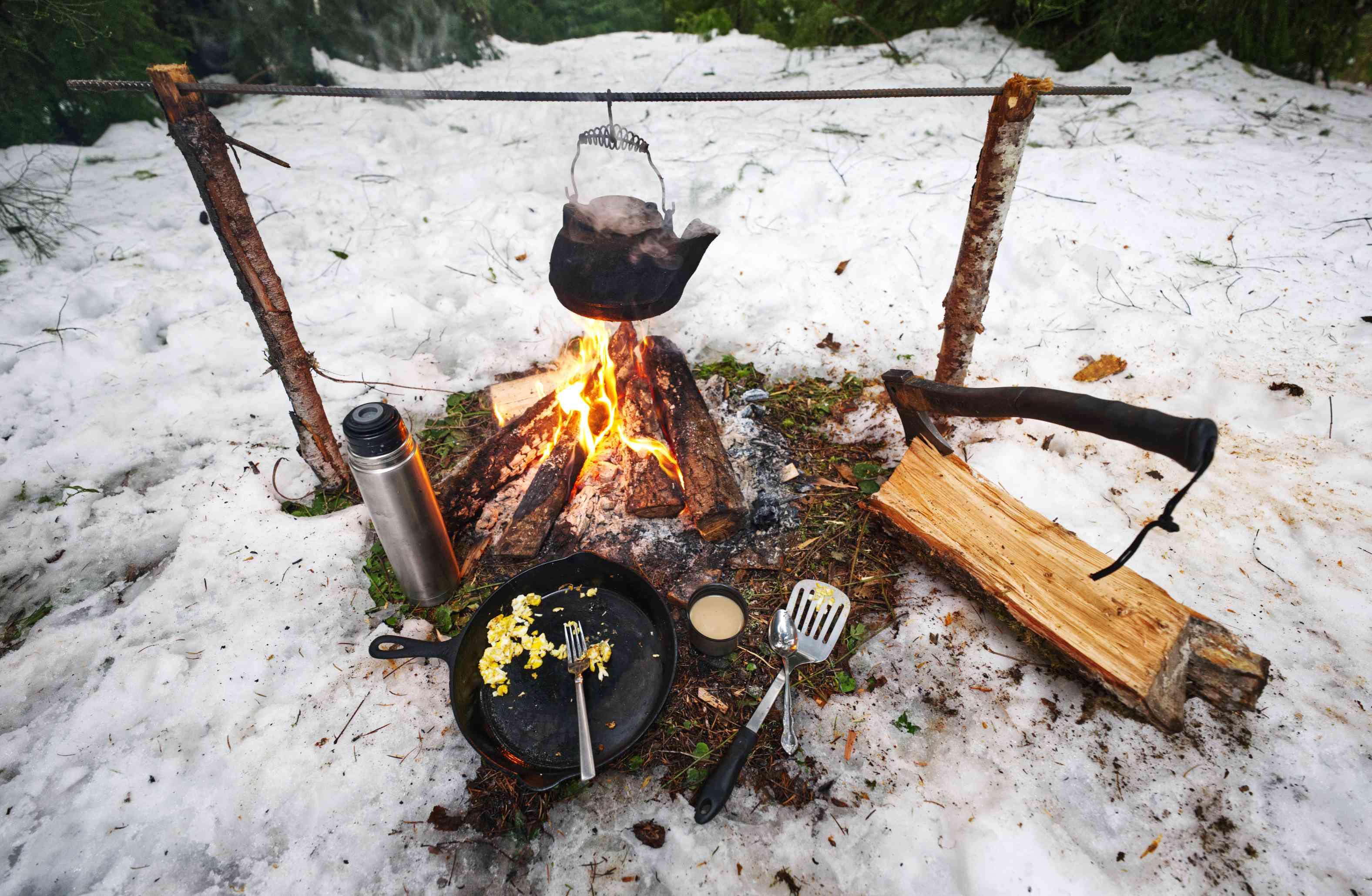 camping kitchen setup with campfire and kettle and cast iron skillet in snow