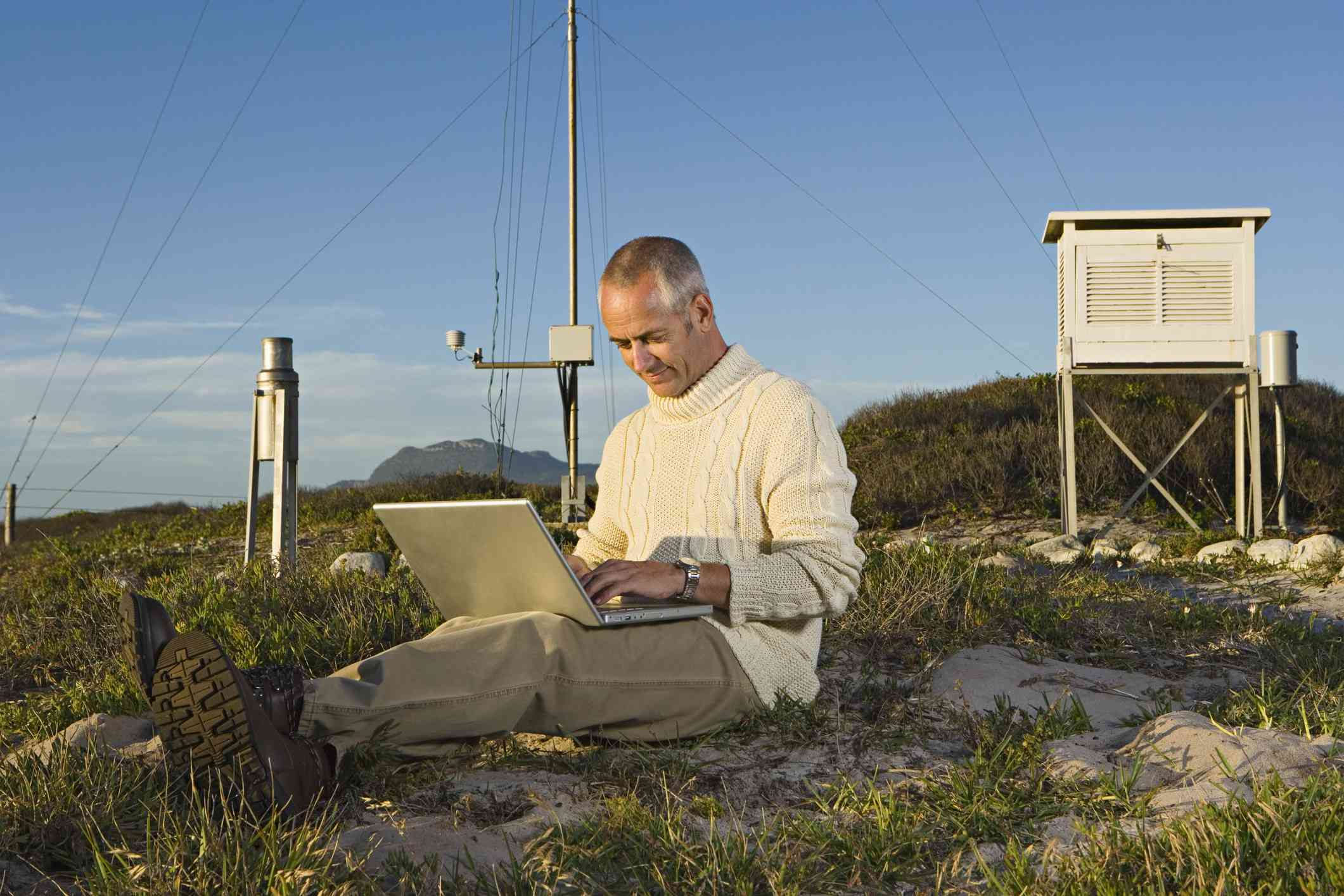 A meteorologist collects data from a mountaintop weather station.