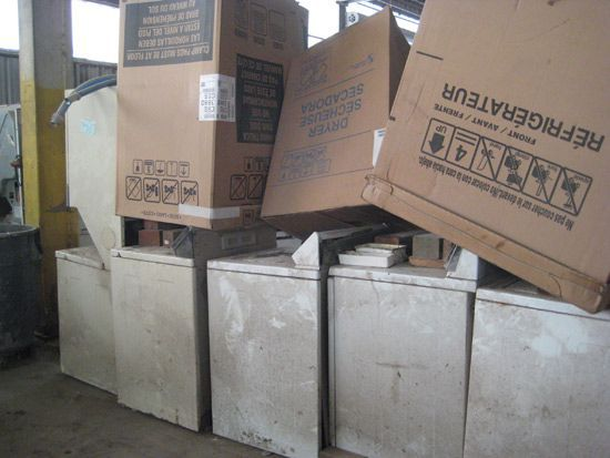 Appliances with large cardboard boxes sitting on top of them in a waste facility .