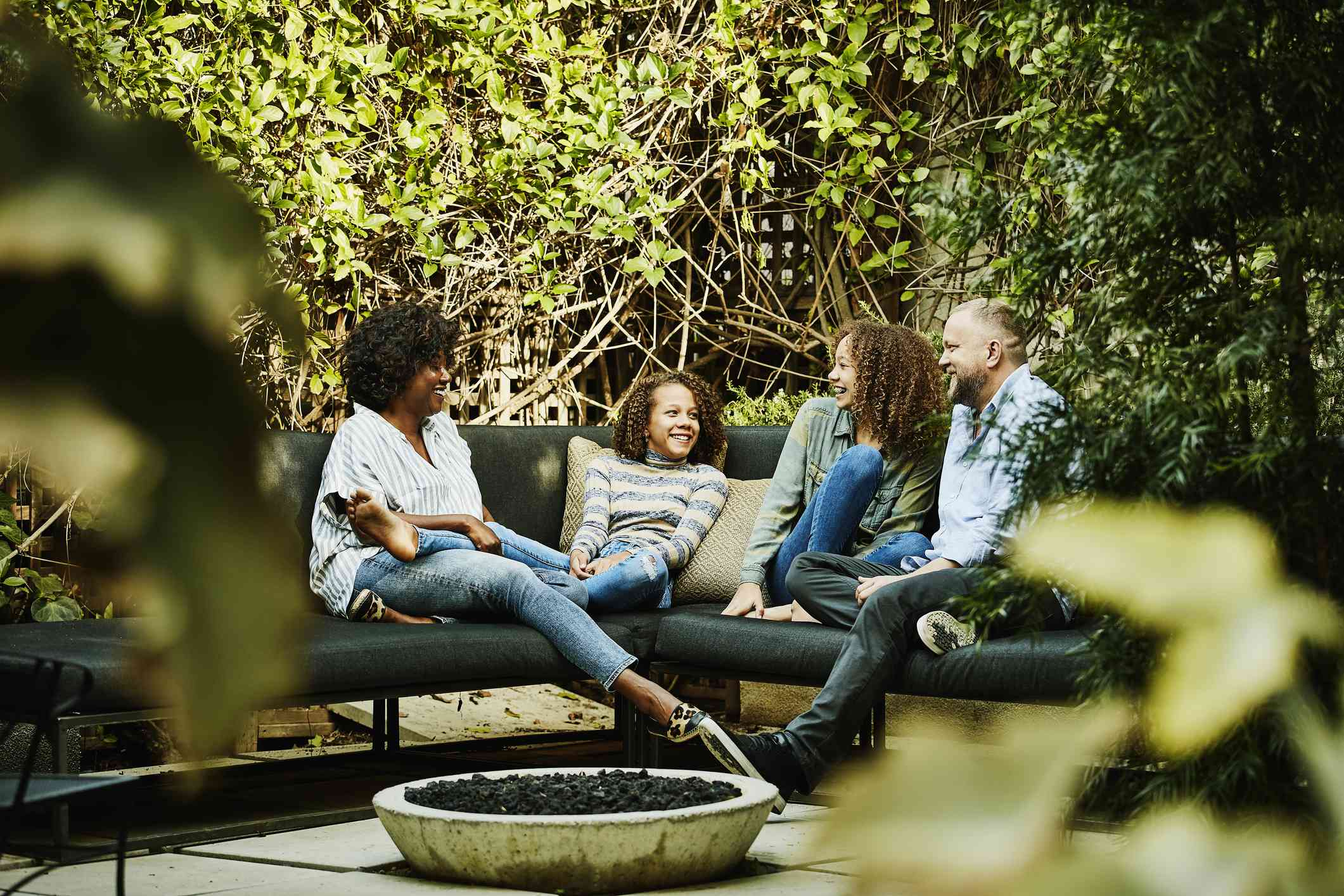 Smiling family hanging out by fire pit in backyard