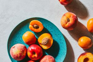cut and whole nectarines, peaches and apricots scattered on speckled turquoise plate