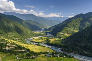 Lush green valley flanked by mountains in Bhutan