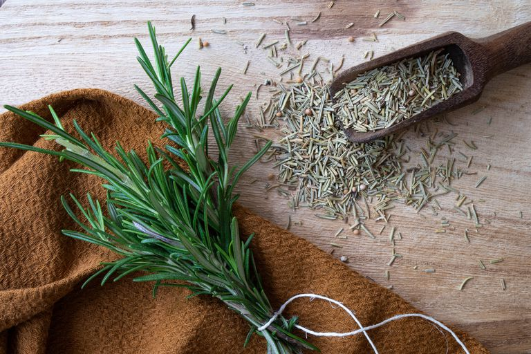 fresh sprig of rosemary tied with twine with spilled dried rosemary on table