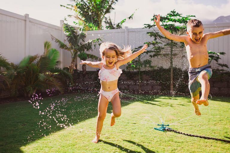 children play in a backyard sprinkler