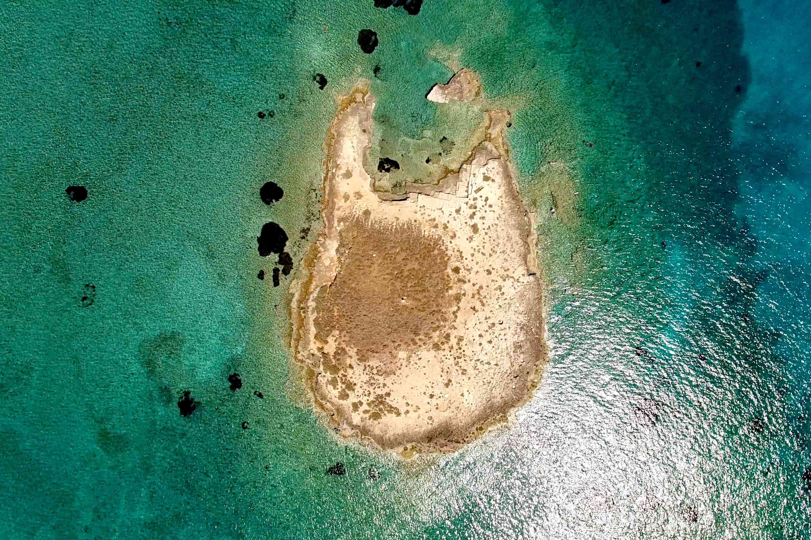 Drone shot of an island and sea containing submerged city