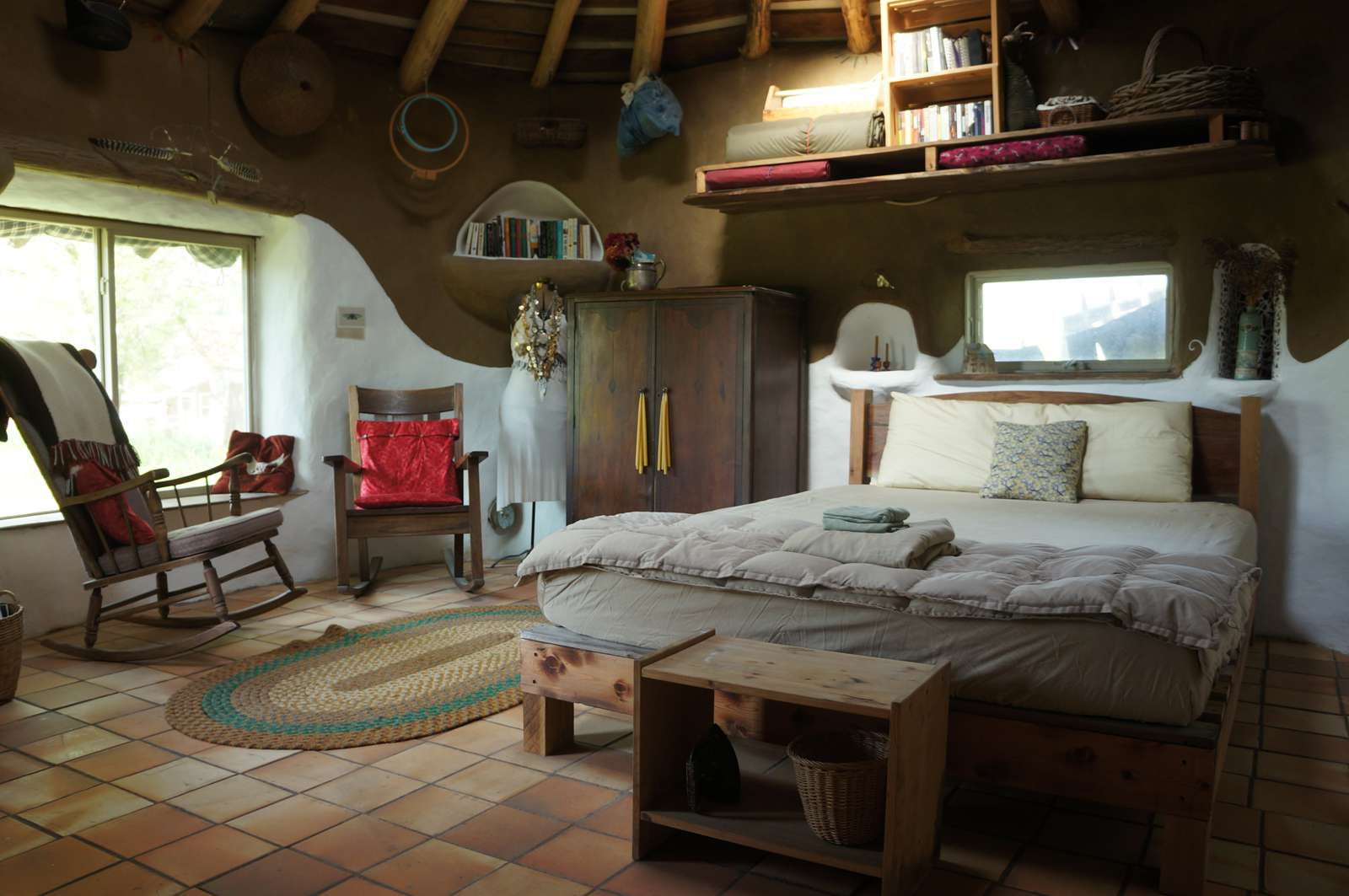 The interior of cob house showing a bedroom set up.