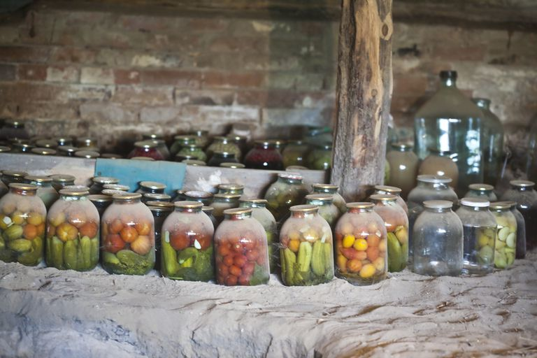 Dusty jars of preserved food in a basement