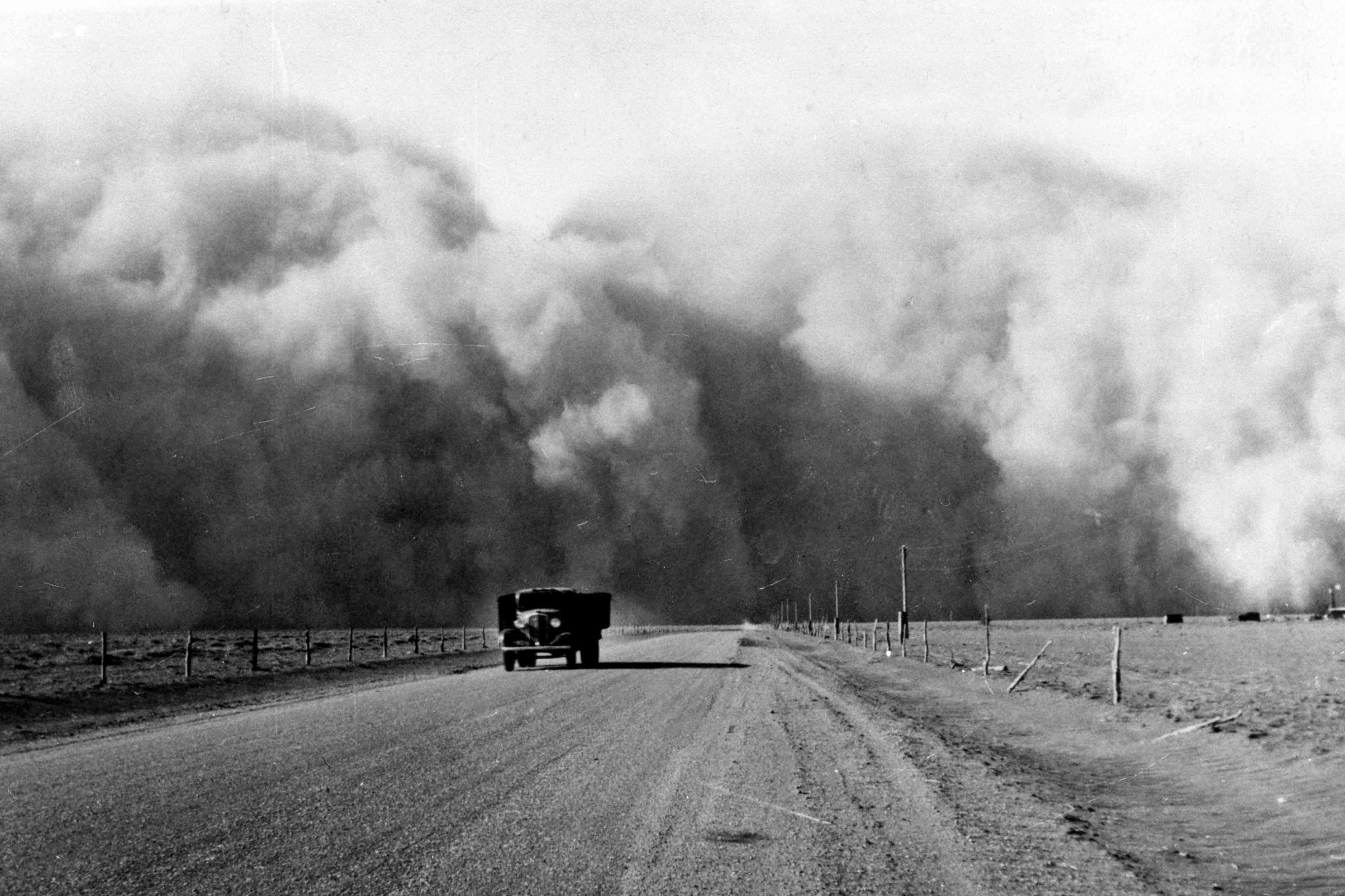 Dust cloud fills the sky and truck drives on dirt road away from it