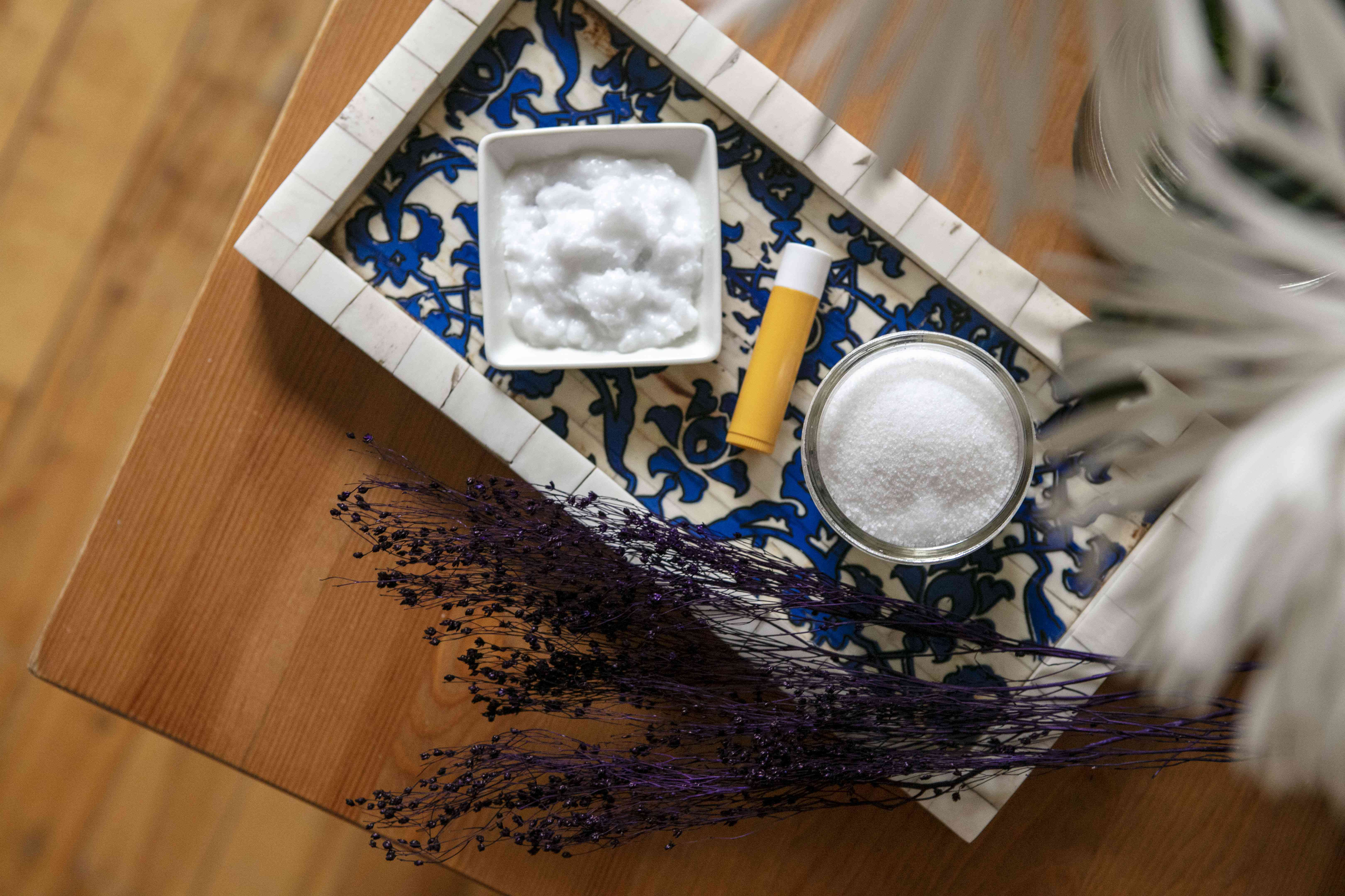 white sugar, lip balm in tube, and coconut oil on tile tray