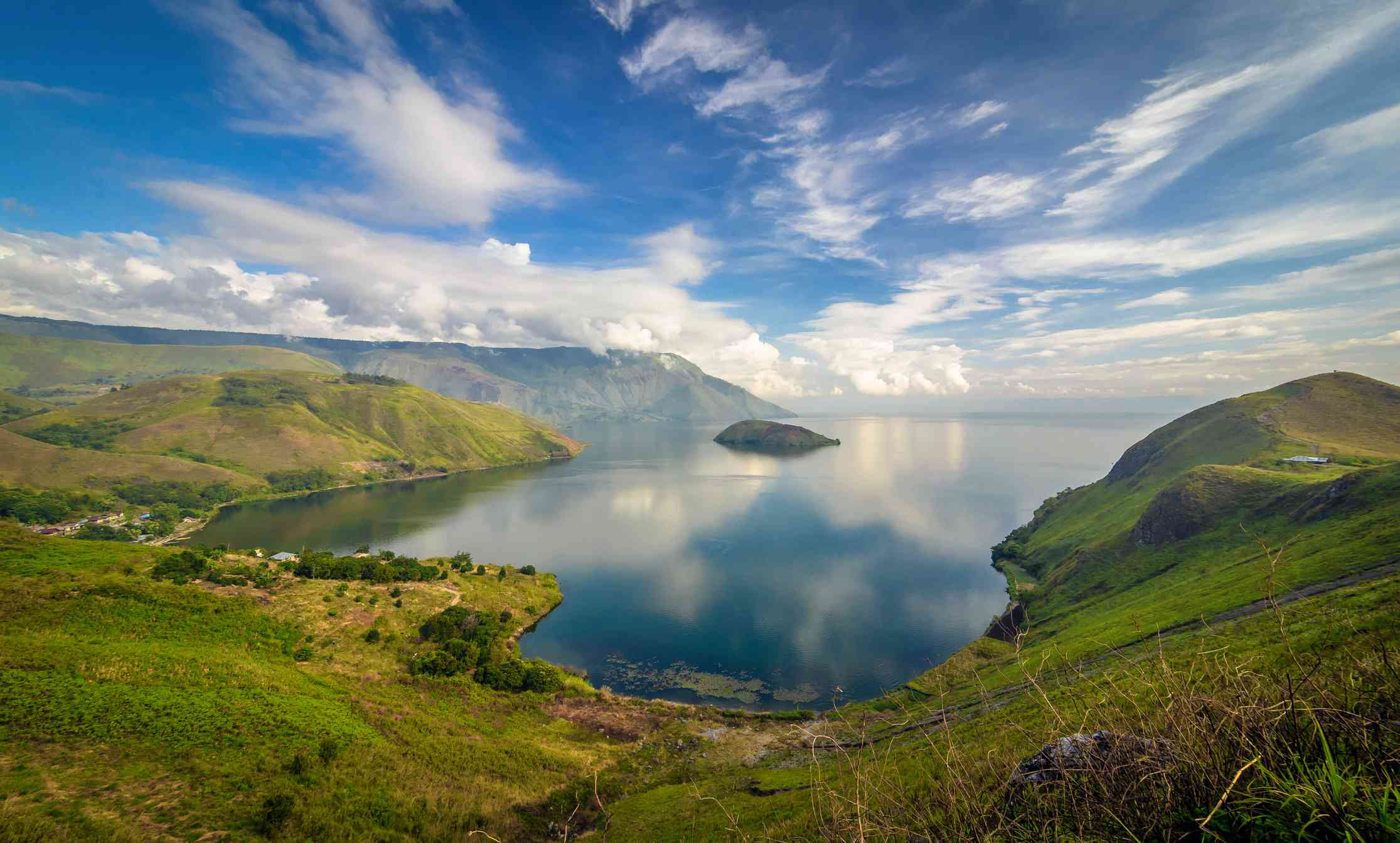 An aerial view of Lake Toba with lush greenery in the foreground.