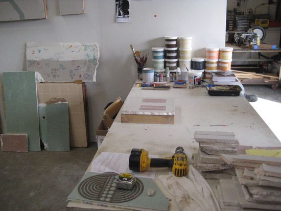 An artist studio with a table full of paint, a drill and tiles.